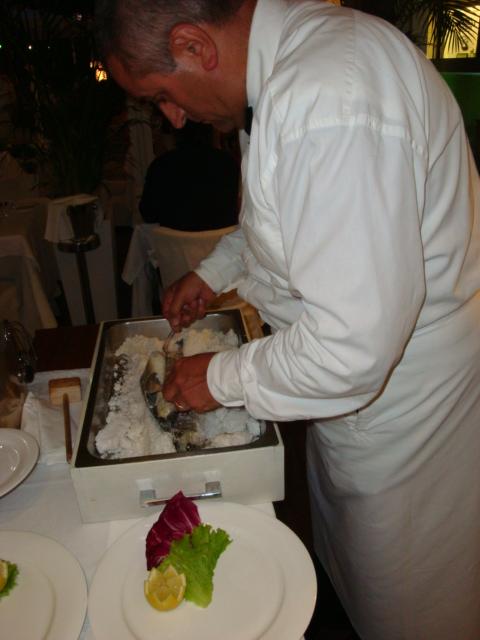 il cameriere pulisce il branzino di Orbetello al sale dolce della salina Camillona di Cervia
