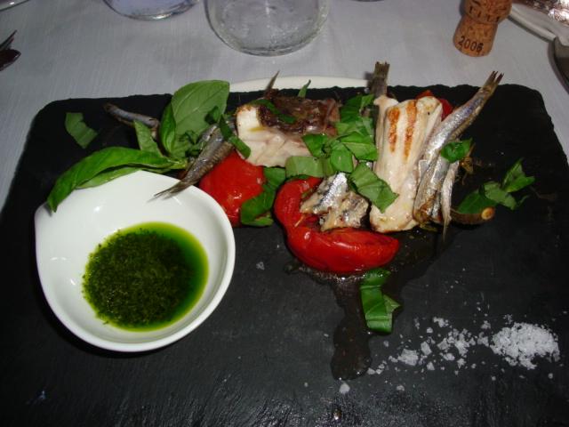 spiedo di acciughe e pesce azzurro su ciappa di ardesia con pomodorini leggermente essicati